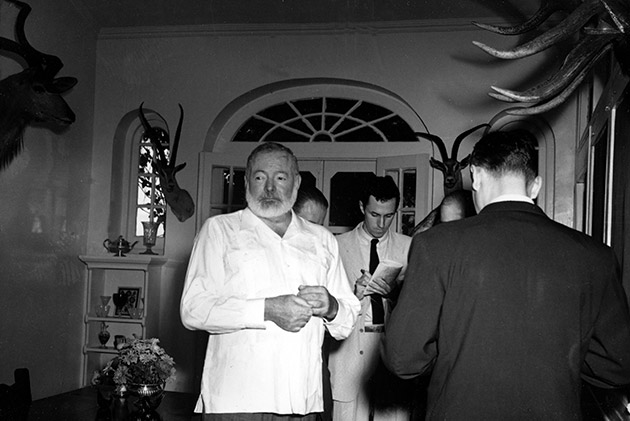 "American novelist Ernest Hemingway meets the press at his Cuban home in San Francisco de Paula, a suburb of Havana, October 28, 1954, after announcement was made that he is awarded the 1954 Nobel Prize in literature. Hemingway said he ""broke the training"" and took a drink to celebrate the honor."