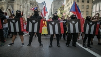 Participants hold signs with the Puerto Rico's flag painted in black and white as symbol of resistance and civil disobedience during the NYC's 60th annual Puerto Rico Day parade on June 11, 2017 in New York City.