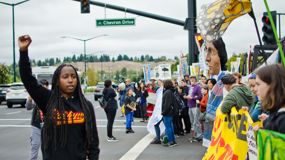 A climate striker with Youth vs. Apocalypse rallies the crowd outside Chevron's headquarters.