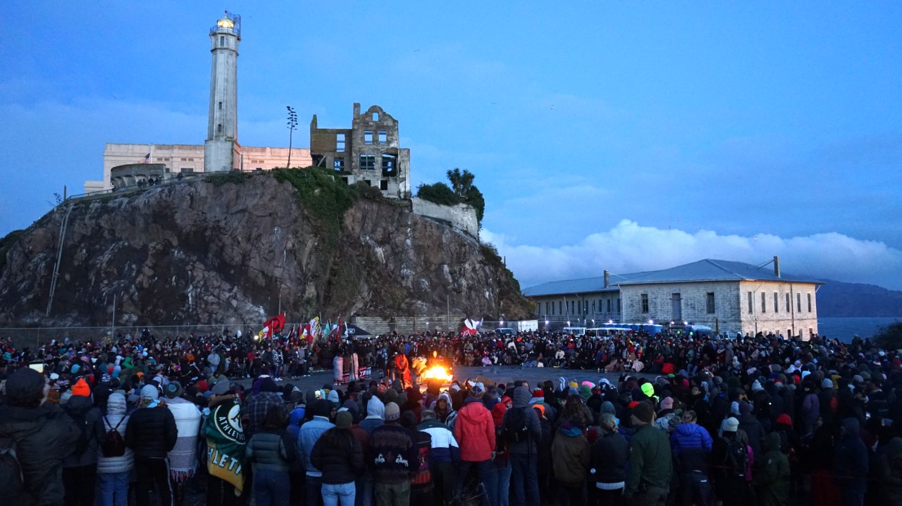 A big crowd of people surrounds a central bonfire, with parts of the Alcatraz penitentiary on a hill in the background.