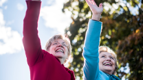 Elizabeth Warren and Hillary Clinton waving