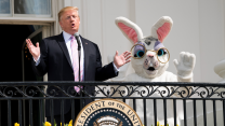 Donald Trump speaks from a White House balcony with an Easter Bunny mascot waving behind him.