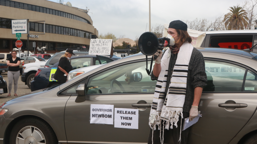 Wearing mask and gloves, plus a kippah and other Jewish garments, person standing outside of a car speaks through a megaphone.