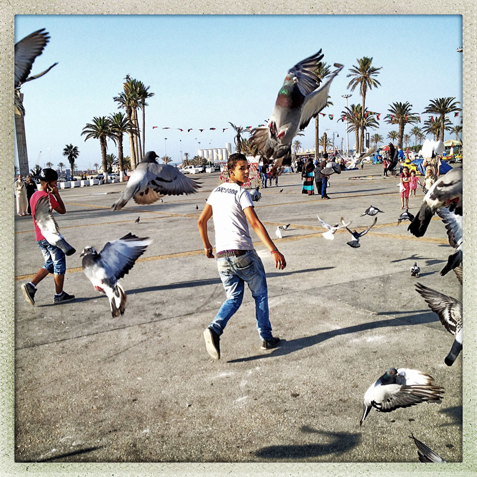 A Libyan teen runs through a flock of birds in the newly renamed Martyrs Square in the center of the Old City in Tripoli.