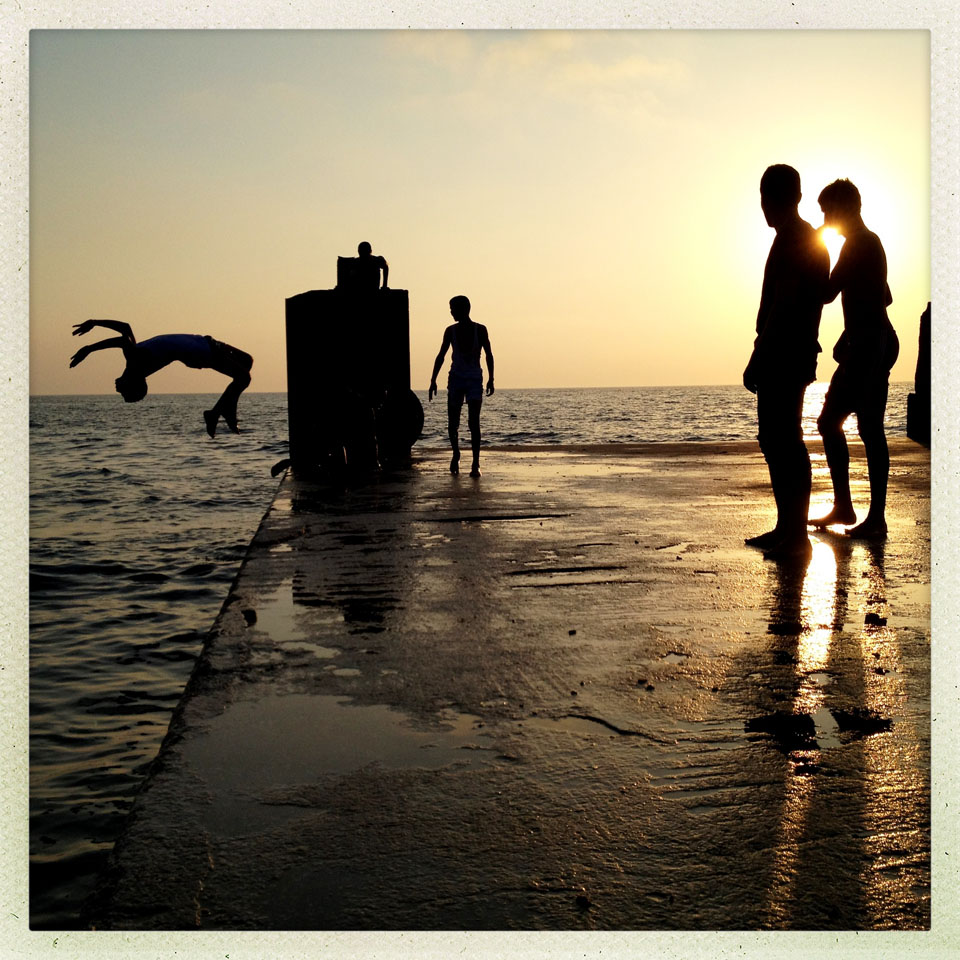Young Libyan men jump into the sea from a concrete dock in Benghazi.